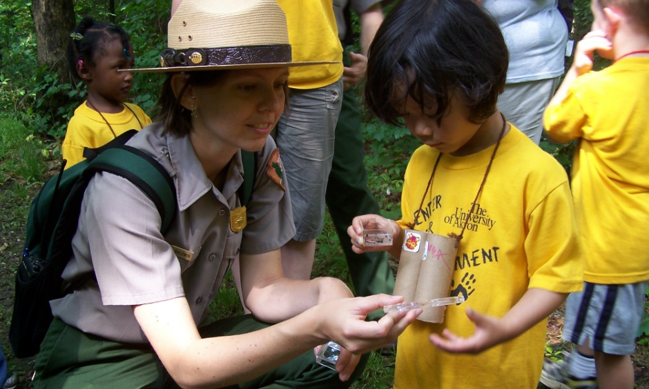 nature hikes and games. ranger and child identifying insects